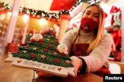 Seorang penjaga toko memberikan barang kepada pelanggan yang berbelanja kebutuhan Natal di tengah pandemi Covid-19 di Roma, Italia, 10 November 2020. REUTERS / Guglielmo Mangiapane