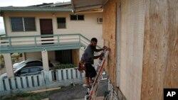 Un habitant pose des planches pour protéger les fenêtres d'une maison en prévision de l'ouragan Lane à Kapolei, Hawaï, le 22 août 2018,