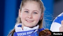 Yulia Lipnitskaya of the gold medal-winning Russian figure skating team poses with her medal during the medal ceremony for the figure skating team ice dance free dance at the Sochi 2014 Winter Olympics, Feb. 10, 2014.