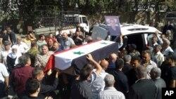 Para pelayat di Suriah Selatan menghadiri acara penguburan massal 216 orang yang tewas akibat serangan ISIS, hari Kamis (26/7).