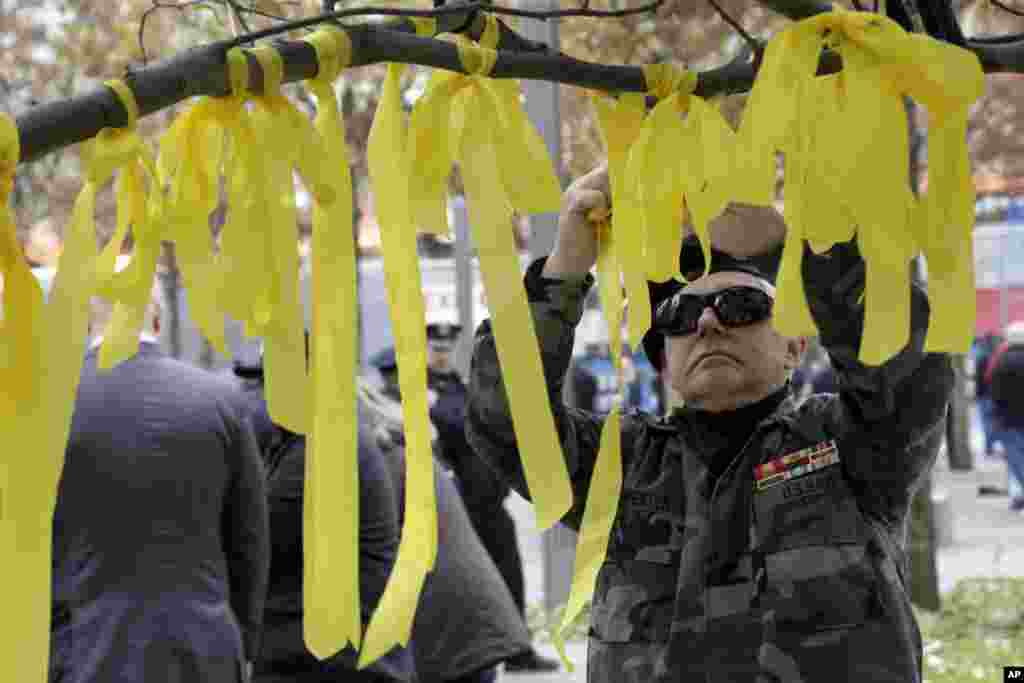 Kevin Carpenter, of Nassau County Chapter 82 of the Vietnam Veterans of America, ties a yellow ribbon to the tree that survived the terror attack, during the Veterans Day observance at the 9/11 Memorial, in New York, November 10, 2012. (AP)