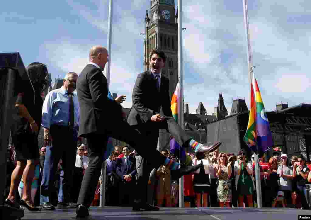 Canada's Prime Minister Justin Trudeau (R) compares socks with Liberal MP Randy Boissonnault during a pride flag raising ceremony on Parliament Hill in Ottawa, Ontario, June 14, 2017.