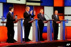 Republican presidential candidate Donald Trump, second from left, gestures as Sen. Marco Rubio, R-Fla., Sen. Ted Cruz, R-Texas, and Ohio Gov. John Kasich look on at a Republican presidential primary debate in Detroit, March 3, 2016.