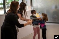 Para guru mencoba untuk mencegah Wendy Otin (6 tahun) dan Oumou Salam Niang (6 tahun) untuk berpelukan saat mereka bertemu pada hari pertama sekolah setelah lockdown, di sebuah sekolah dasar di Barcelona, Spanyol, 8 Juni 2020. (Foto: dok).