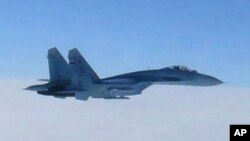 FILE - In this photo taken by Japan Air Self-Defense Force and released by the Joint Staff Office of the Defense Ministry of Japan, a Russian fighter jet SU-27 flies over the sea off the Japanese island of Hokkaido Thursday afternoon, Feb. 7, 2013.