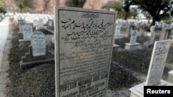 "FILE - The word ""Muslim"" has been painted over by vigilantes, on the tombstone of Pakistani scientist Abdus Salam, a member of the Ahmadi community and Pakistan's only Nobel laureate, in the Ahmadi graveyard in the town of Rabwa, Dec. 9, 2013. A recent assassination victim in Pakistan was a relative of Salam."
