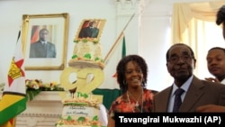Zimbabwean President Robert Mugabe and his wife, Grace, stand next to his birthday cake at State House in Harare, Monday, Feb. 22, 2016. Office staff in the president's office organized a surprise birthday celebration ahead of bigger birthday celebration set for Saturday in the southern town of Masvingo. (AP Photo/Tsvangirayi Mukwazhi)