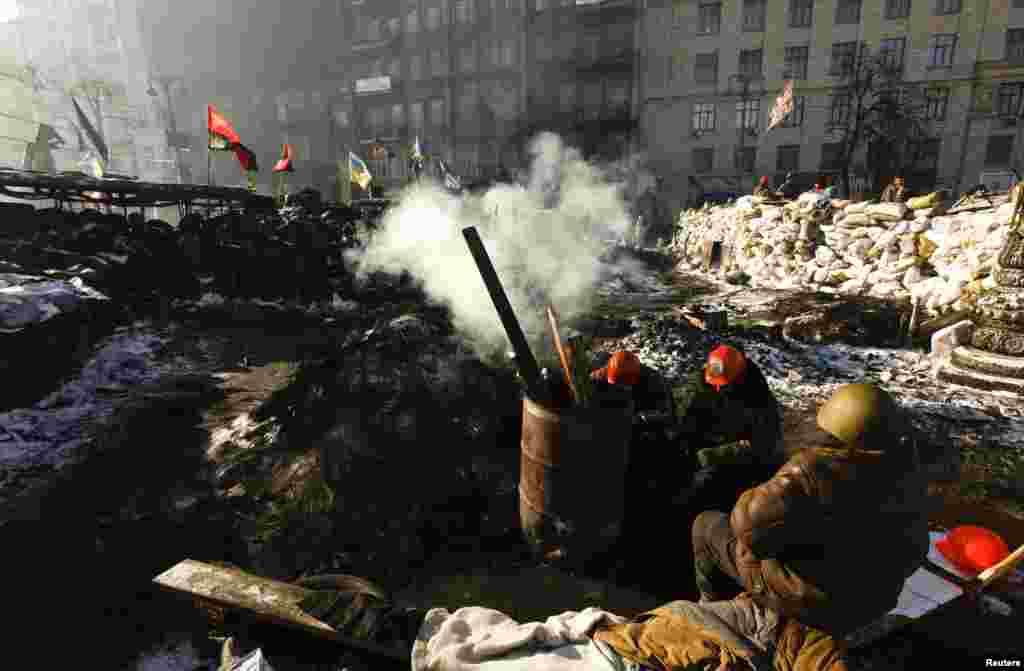 سنگربندی مخالفان در برابر نیروهای دولتی در نزدیکی محل درگیری با پلیس ضدشورش در هوای بیست درجه زیر صفر - کیف، ۳۰ ژانویه ۲۰۱۴