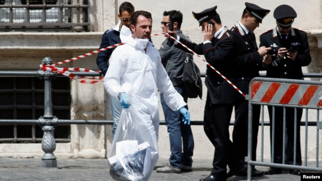 A forensic investigator (in foreground) is seen surveying the crime scene outside the Italian prime minister's office in Rome April 28, 2013.