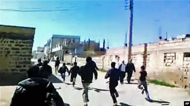 This image made from amateur video purports to show Syrian protesters running in Daraa, Syria, March 12, 2012.