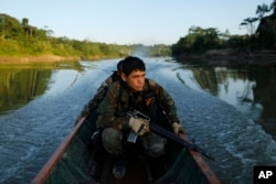 FILE - Counternarcotics police special forces cross a river on a boat after blowing a hole in a clandestine airstrip used by drug traffickers in Ciudad Constitucion, Peru, July 28, 2015.