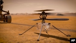 This illustration made available by NASA depicts the Ingenuity Mars Helicopter on the red planet's surface near the Perseverance rover, left. NASA is upping the ante with its newest rover headed to Mars. (NASA/JPL-Caltech via AP)