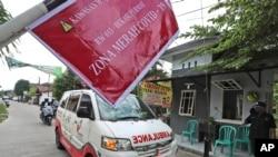 """Ambulans mengangkut jenazah korban COVID-19 melewati penanda """"Kawasan Merah"""" menuju lokasi pemakaman di Bekasi, 11 Juli 2021. (AP Photo/Achmad Ibrahim)"""