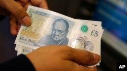 Pegawai Halifax bank di London memperlihatkan lembaran uang 5 pound sterling baru yang terbuat dari polimer, saat diluncurkan 13 September 2016. (AP/Alastair Grant)
