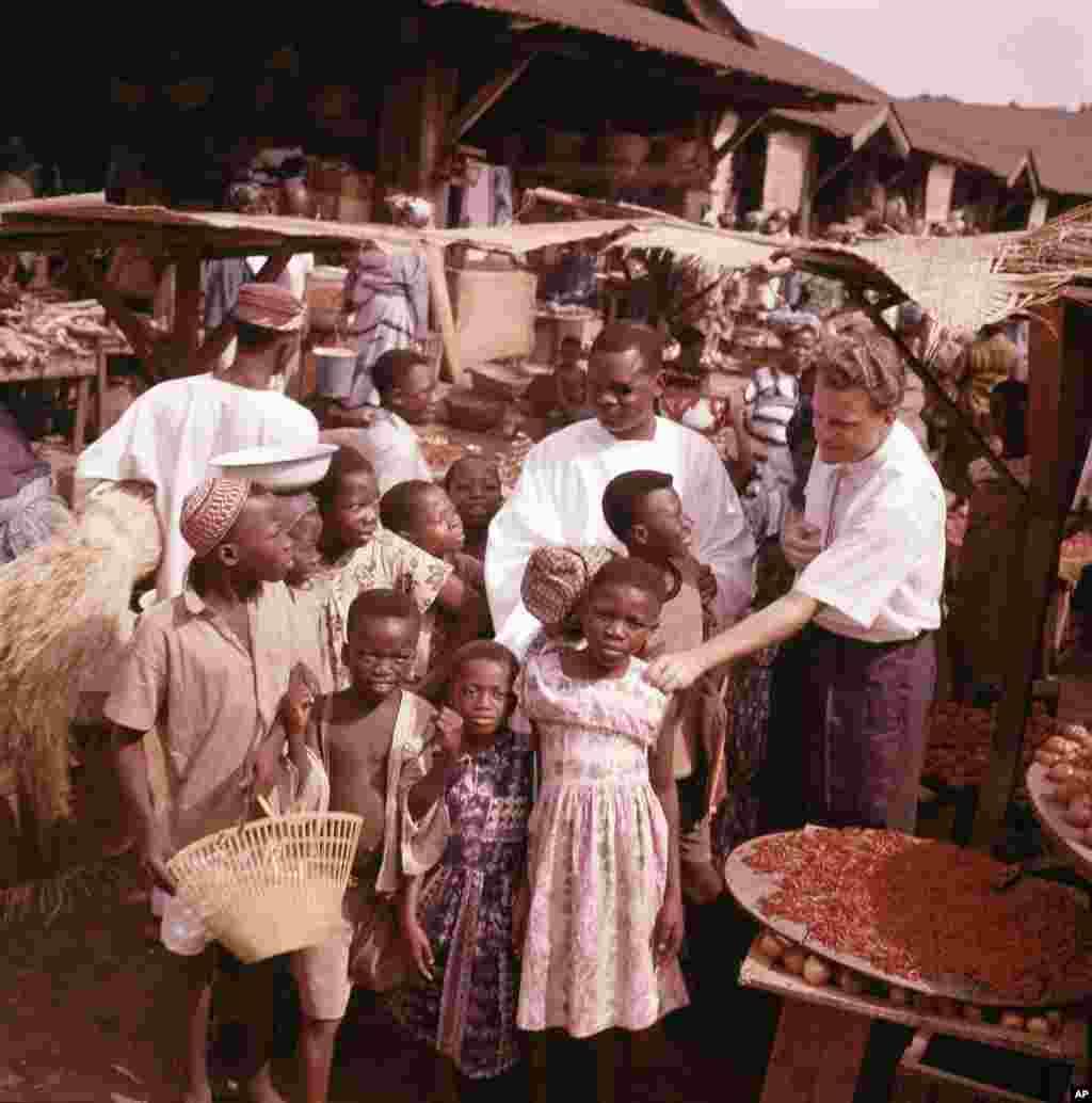 Billy Graham est pris en photo avec des enfants lors d'une visite dans un village, au Ghana, en janvier 1960.