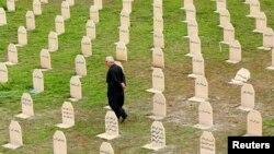 یک شهروند کرد عراقی در حال بازدید از گورستان قربانیان عملیات «انفال» رژیم صدام حسین - ۱۶ مارس ۲۰۱۴ سلیمانیه، اقلیم کردستان عراق