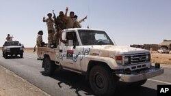 反卡扎菲的戰鬥人員星期五從班尼瓦里出來後經過檢查站
