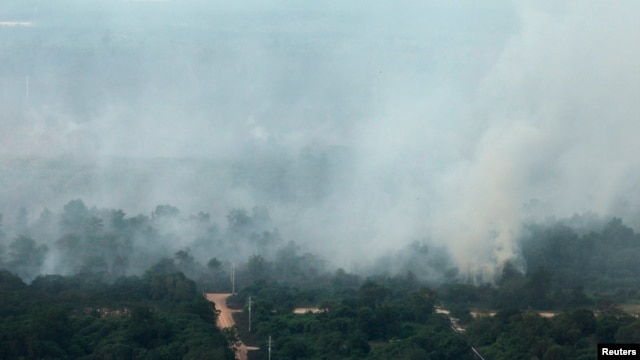 FILE - An aerial view of smoke rising from burnt trees during haze in Indonesia's Riau province, June 28, 2013.