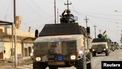 Peshmerga forces ride on military vehicles in the town of Bashiqa, after it was recaptured from the Islamic State, east of Mosul, Iraq, Nov. 9, 2016.