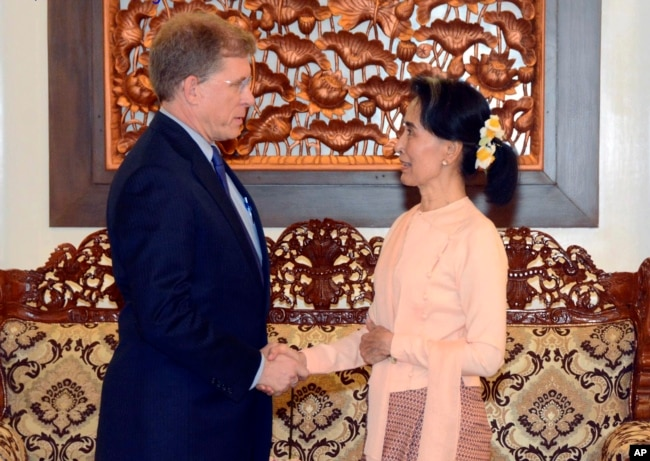 In this photo released by Myanmar Foreign Ministry, Myanmar's State Counselor Aung San Suu Kyi, right, shakes hands with U.S. State Department's Deputy Assistant Secretary for Southeast Asia Patrick Murphy, in Naypyitaw, Myanmar, Sept. 19, 2017.