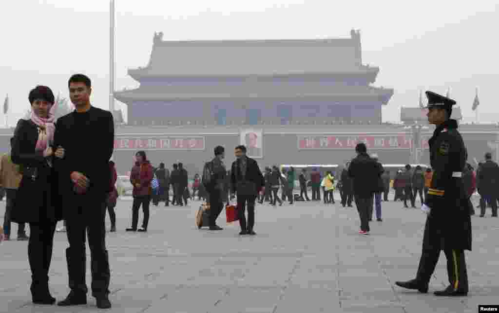 A paramilitary soldier patrols near visitors posing for souvenir pictures at Tiananmen Square, Beijing, China, Nov. 1, 2013.