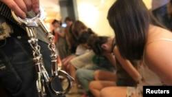 Cảnh sát Trung Quốc cầm còng sau vụ đột kích một ổ mại dâm ở Ôn Châu, tỉnh Chiết Giang.
