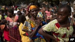 Women wait in line to have their children vaccinated against measles, at a makeshift camp housing people displaced by violence at a monastery in the Boy Rabe district of Bangui, Central African Republic, Sunday, Jan. 5, 2014. Concerned that crowded and un