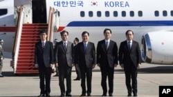 韩国高级国家安全顾问郑义荣(中)、韩国国家情报院院长徐薰(左二)与韩国代表团其他成员在首尔的一个军事基地登机前合影。(2018年3月5日)