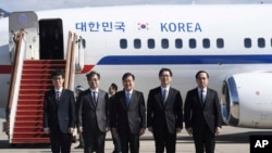 South Korea's national security director Chung Eui-yong, center, National Intelligence Service Chief Suh Hoon, second left, and other delegators pose before boarding an aircraft as they leave for Pyongyang at a military airport in Seongnam, south of Seoul, Monday, March 5, 2018. A group of high-level South Korean officials has left for North Korea for talks on North Korea's nuclear program and ways to help resume talks between Pyongyang and Washington.