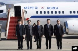 South Korea's national security director Chung Eui-yong, center, National Intelligence Service Chief Suh Hoon, second left, and other delegators pose before boarding an aircraft as they leave for Pyongyang at a military airport.