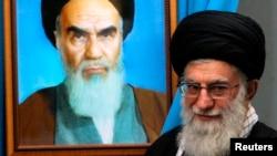 El Líder Supremo iraní, Ali Khamenei, junto a una pintura de su predecesor, el fallecido Ayatollah Khomenei.
