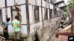 Indian people inspect a house damaged by vandals in Kokrajhar, India, July 23, 2012.