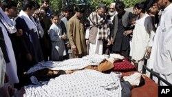 Dân làng Afghanistan đứng cạnh thi thể của các nạn nhân được cho là đã thiệt mạng trong cuộc đột kích của của NATO và Afghanistan tại Laghman, ngày 1/5/2012