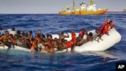 Migrants dans un canot pneumatique approchés par l'Aquarius de SOS Meditrranée au large des côtes de l'île italienne de Lampedusa, le 17 avril 2016.