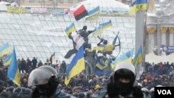 Pengunjuk rasa integrasi pro-Uni Eropa berdiri di belakang barisan polisi anti huru hara di Lapangan Kemerdekaan di Kiev, Ukraina (11/12).
