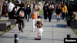 2020年4月3日戴著口罩的女孩在南韓首爾公園騎踏板車。