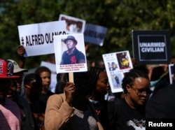 FILE - Demonstrators hold a march and rally to protest the fatal police shooting of Ugandan immigrant Alfred Olango in El Cajon, California, Oct. 1, 2016.