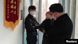 Friends of human right activist Cao Shunli stand in front of an intensive care unit where Cao is hospitalized as they are not allowed to go inside. Beijing, China, Mar. 1, 2014.