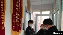 Tidak diijinkan masuk, teman-teman aktivis Cao Shunli berdiri di depan rumah sakit di mana Cao sempat dirawat di Beijing, China, 1/3/2014. Cao tewas di penjara di mana ia tidak diberikan perawatan medis.