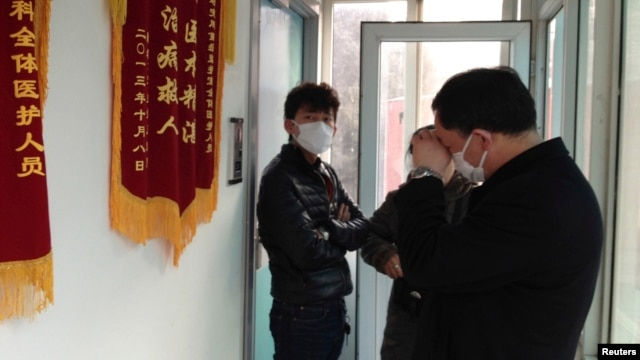 Friends of human right activist Cao Shunli stand in front of an intensive care unit where Cao was hospitalized at a hospital in Beijing on March 1, 2014.