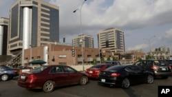 រថយន្តតម្រង់ជួរគ្នានៅមុខទីស្នាក់ការកណ្តាលរបស់សាជីវកម្មប្រេងសាំងជាតិរបស់នីហ្សេរីយ៉ា (Nigerian National Petroleum Corporation) ដើម្បីទិញប្រេងនៅក្នុងក្រុងអាប៊ូហ្សា (Abuja) ប្រទេសនីហ្សេរីយ៉ា កាលពីថ្ងៃទី២៦ ខែឧសភា ឆ្នាំ២០១៥។