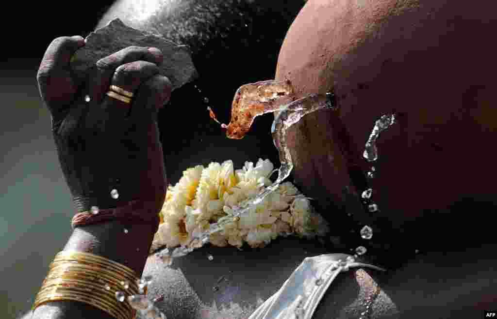 Một người bà con dùng hòn đá khoét lỗ nơi bình đựng nước của Sudhakar Reddy, một trong những người chết trong vụ đánh bom ở thành phố Hyderabad của Ấn Độ.