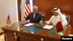 Le ministre des Affaires étrangères du Qatar, Cheikh Mohammed bin Abdulrahman al-Thani, à droite, et le Secrétaire d'État américain Rex Tillerson, signent un mémorandum d'accord à Doha, au Qatar, le 11 juillet 2017.
