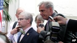 House Majority Leader Kevin McCarthy of California, right, and Rep. Patrick McHenry, R-NC, left, race past reporters on Capitol Hill, Washington, Sept. 25, 2015.