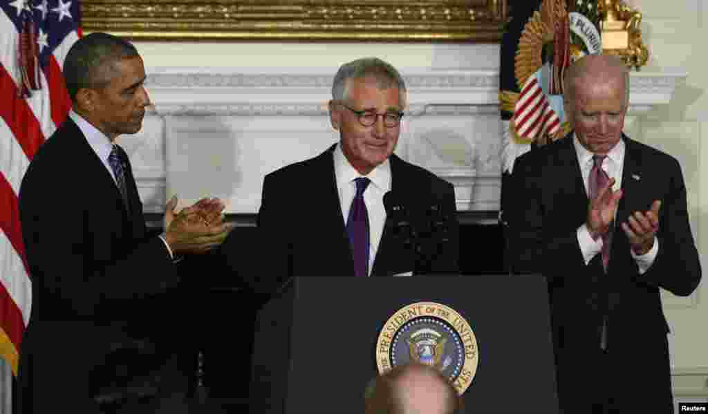 U.S. President Barack Obama and Vice President Joe Biden (R) applaud Defense Secretary Chuck Hagel after the president announced Hagel's resignaton at the White House in Washington, Nov. 24, 2014.