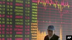 投資者走過上海證券公司的股市行情屏幕。