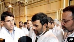 Iranian President Mahmoud Ahmadinejad listens to a technician during his visit of the Natanz Uranium Enrichment Facility, 8 Apr 2008