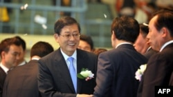 South Korean Prime Minister Kim Hwang-Sik (C) shakes hands with guests during a launch ceremony in Sejong City, south of Seoul, July 2, 2012.