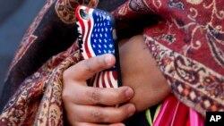 Une femme tient un téléphone portable avec une coque du drapeau des Etats-Unis, le vendredi 4 décembre 2015. (AP Photo / Jacquelyn Martin)