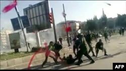 نیروهای امنیتی یک دانشجوی دانشگاه حلب را کتک می زنند. تصویر از یک ویدئوی منسوب به درگیری در ۱۷ مه است.